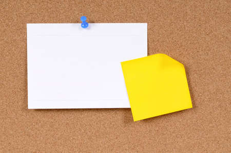 sticky notepaper: Office index card and sticky note pinned to a cork bulletin board. Stock Photo