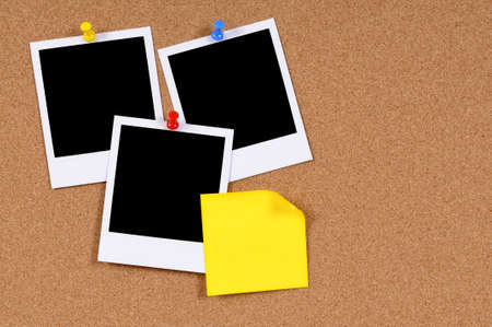 corkboard: Blank photo prints with yellow sticky note pinned to a cork bulletin board.