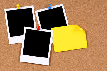 white polaroids: Blank photo prints with yellow sticky note pinned to a cork bulletin board.