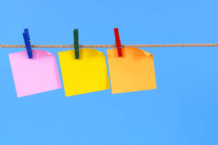peg board: Blank office sticky notes hanging on a rope or washing line against a blue craft paper background (please note that the paper background has a slightly mottled texture). Stock Photo