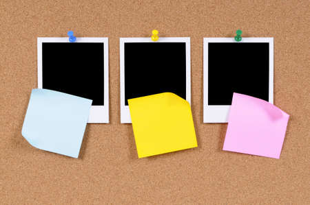 Blank photo prints with sticky notes pinned to a cork bulletin board. photo