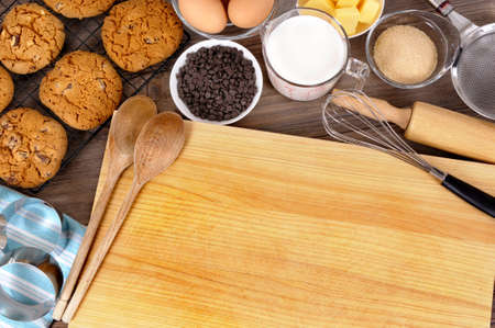 milk and cookies: Freshly made chocolate chip cookies on a dark wood table with chopping board and ingredients.