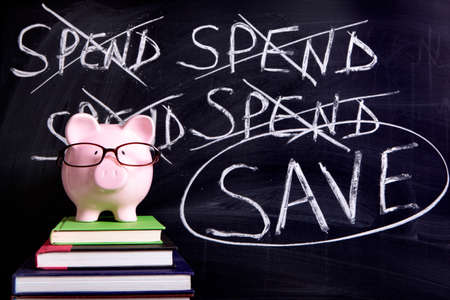 untidy: Pink piggy bank with glasses standing on books next to a blackboard with untidy spending and saving message.  Sharp focus on the piggy bank with blackboard slightly blurred.