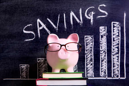 retirement nest egg: Pink piggy bank with glasses standing on books next to a blackboard with savings growth chart.  Sharp focus on the piggy bank. Stock Photo