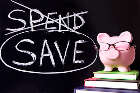spend: Pink piggy bank with glasses standing on books next to a blackboard with simple spend and save message.