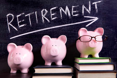 retirement savings: Three pink piggy banks standing on books next to a blackboard with retirement savings message.  Sharp focus on the piggy banks. Stock Photo