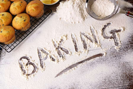 The word Baking written in flour on a dark wood table with freshly baked muffins and ingredients.