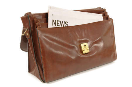 broadsheet: Old leather briefcase with newspaper set against a white background