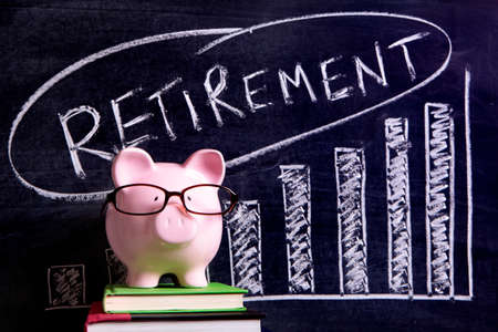 Pink piggy bank with glasses standing on books next to a blackboard with retirement savings message.  Sharp focus on the piggy bank with blackboard slightly blurred. Stock Photo