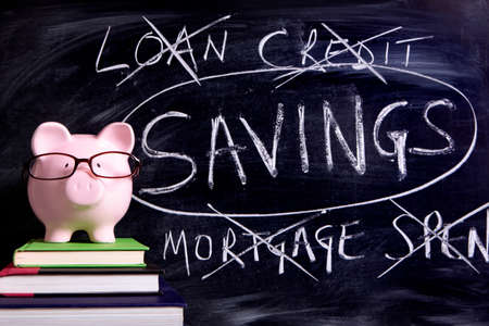 borrowing: Pink piggy bank with glasses standing on books next to a blackboard with untidy borrowing and savings message.  Sharp focus on the piggy bank.