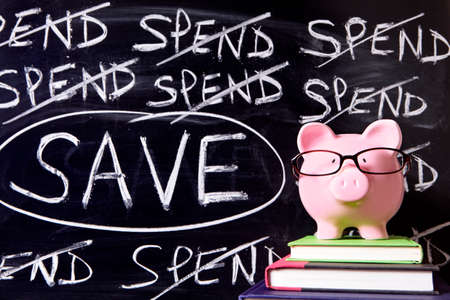 untidy: Pink piggy bank with glasses standing on books next to a blackboard with untidy spending and saving message.