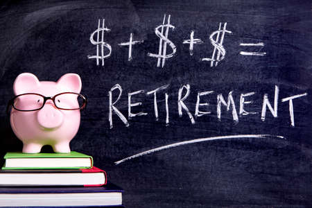 Pink piggy bank with glasses standing on books next to a blackboard with simple retirement formula.  Sharp focus on the piggy bank.