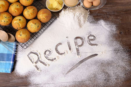The word Recipe written in flour on a dark wood table with freshly baked muffins and ingredients. photo