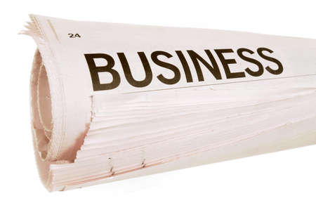 newsprint: Rolled up newspaper with business headlines set against a white background Stock Photo