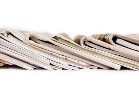 broadsheet: Row of folded newspapers with magazine supplements tucked inside