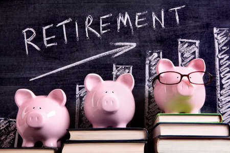 Three pink piggy banks standing on books next to a blackboard with retirement savings chart.  Sharp focus on the piggy banks.