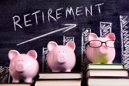 Trzy różowe świnki skarbonki stojącej na książki obok tablicy z wykresu oszczędności emerytalne. Sharp skoncentrować się na skarbonki.