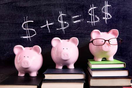 Tres huchas rosados ??que se colocan en los libros junto a una pizarra con matemáticas simple dinero. Foco sostenido en las huchas.