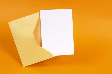letter envelopes: Sobre de oro met�lico con carta de tarjeta de mensaje en blanco o invitaci�n aislados en un fondo anaranjado. Foto de archivo