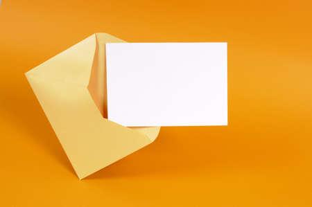 apertura: Sobre de oro metálico con carta de tarjeta de mensaje en blanco o invitación aislados en un fondo anaranjado. Foto de archivo