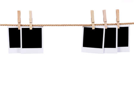 Several blank instant camera photo prints hanging on a rope or washing line isolated against a blue background.  Space for copy.
