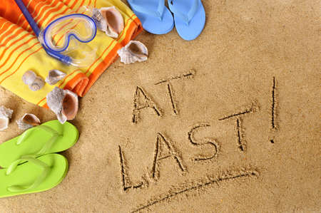 retiring: Beach background with towel and flip flops and the words At Last! written in sand. Stock Photo