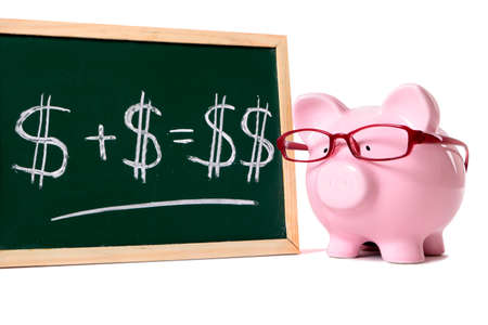 Pink piggy bank with glasses standing next to a blackboard with simple money math isolated on a white background.