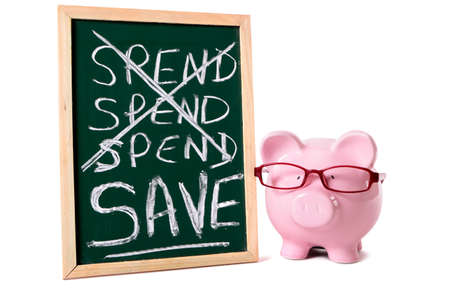 Pink piggy bank with glasses standing next to a blackboard with spend and save message isolated on a white background. photo