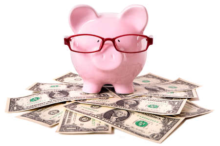 untidy: Pink piggy bank with glasses standing on an untidy pile of one dollar bills isolated on a white background.