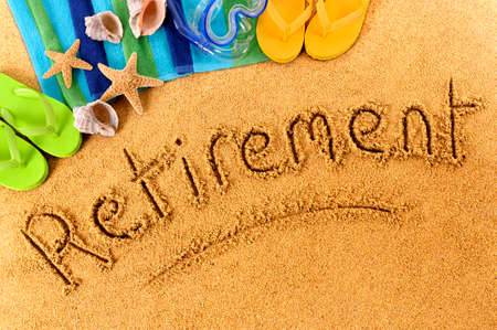 word: Beach background with towel and flip flops and the word Retirement written in sand.