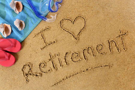retiring: Beach background with towel and flip flops and the words I Love Retirement written in sand.