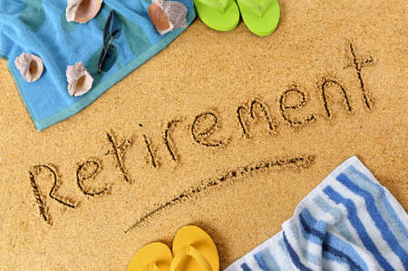 retiring: Beach background with towel and flip flops and the word Retirement written in sand.
