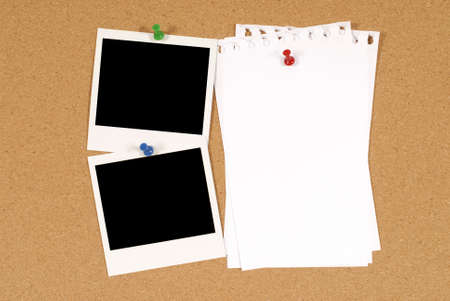 Cork notice or bulletin board with two blank instant camera photo prints and several sheets of untidy torn notepaper. Space for copy.