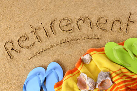 Beach background with towel and flip flops and the word Retirement written in sand. photo