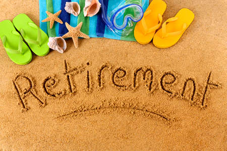 retirement age: The word Retirement written on a sandy beach, with scuba mask, beach towel, starfish and flip flops. Stock Photo