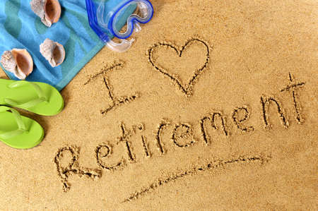 scuba mask: The words I Love Retirement written on a sandy beach, with scuba mask, beach towel, starfish and flip flops. Stock Photo