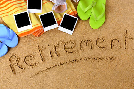 retirement age: Beach background with towel, flip flops, blank photo prints and the word Retirement written in sand. Stock Photo