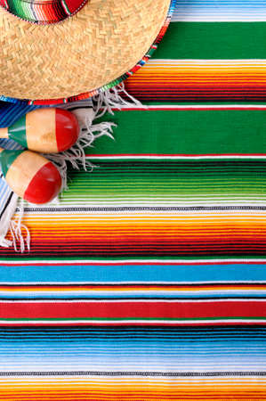 Mexican background with sombrero straw hat, maracas and traditional serape blanket or rug.  Space for copy.