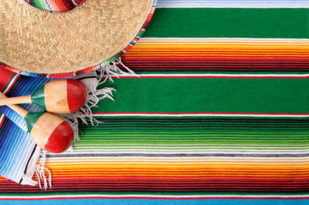 serape: Mexican background with sombrero straw hat, maracas and traditional serape blanket or rug.  Space for copy.