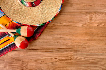 Mexican background with sombrero straw hat, maracas and traditional serape blanket or rug on a wood floor.  Space for copy. 스톡 콘텐츠
