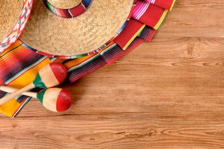sombrero de charro: Fondo mexicano con sombrero sombrero de paja, maracas y una manta sarape tradicional o una alfombra en un piso de madera. Espacio para la copia.