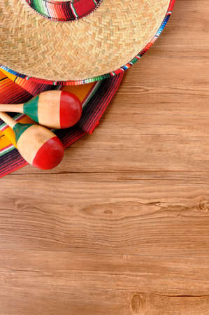 mexican sombrero: Mexican background with sombrero straw hat, maracas and traditional serape blanket or rug on a wood floor.  Space for copy. Stock Photo