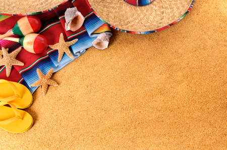 Mexican beach background with sombrero straw hat, traditional serape blanket, starfish, seashells and maracas.  Space for copy.