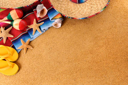 Mexican beach background with sombrero straw hat, traditional serape blanket, starfish, seashells and maracas.  Space for copy. photo