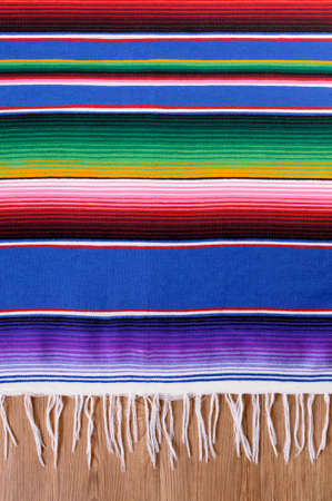 Mexican background with traditional serape blanket or rug on a wood floor.  Space for copy. Reklamní fotografie