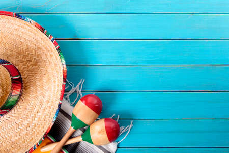 Mexican sombrero and maracas with traditional serape blanket laid on an old blue painted pine wood floor.  Space for copy. Standard-Bild