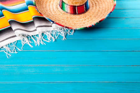 serape: Mexican sombrero and traditional serape blanket laid on an old blue painted pine wood floor.  Space for copy.