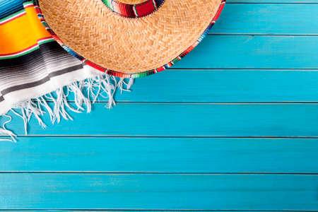 chapeau de paille: Sombrero mexicain et couverture de serape traditionnelle posé sur un vieux plancher de bois peint de pin bleu. Espace pour la copie. Banque d'images