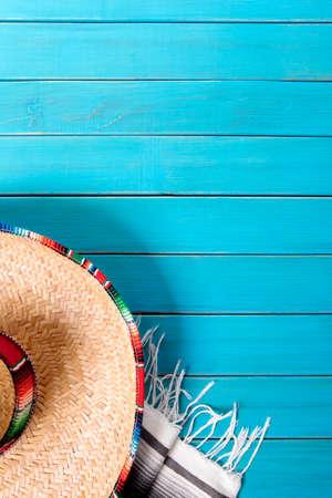 メキシコのソンブレロと伝統的なセラーベ毛布は、古い青い塗られた松の木の床に置いた。 コピーのためのスペース。 写真素材