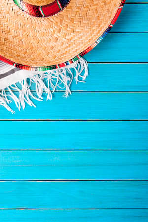 mexican background: Mexican sombrero with traditional serape blanket laid on an old blue painted pine wood floor.  Space for copy.